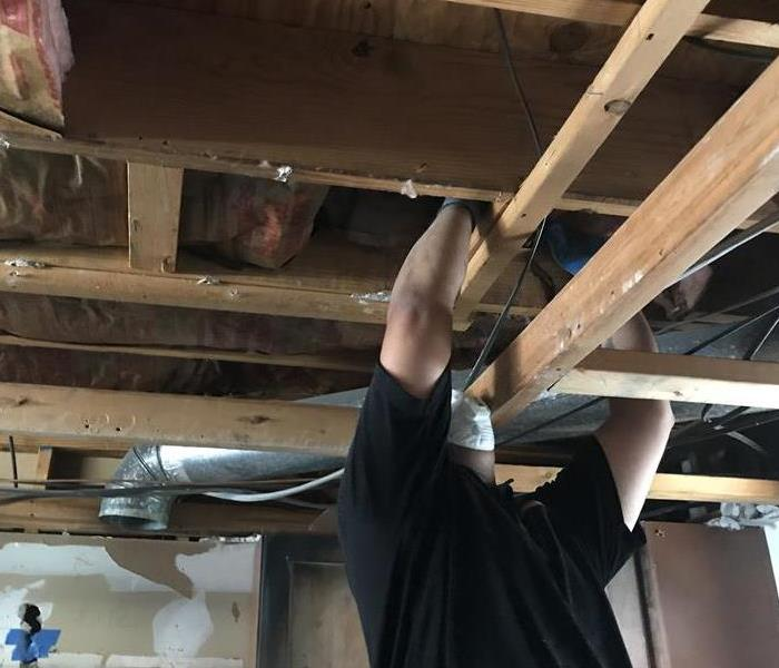a man working on a ceiling with exposed wood beams