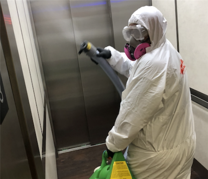 a man with an electrostatic sprayer disinfecting an elevator
